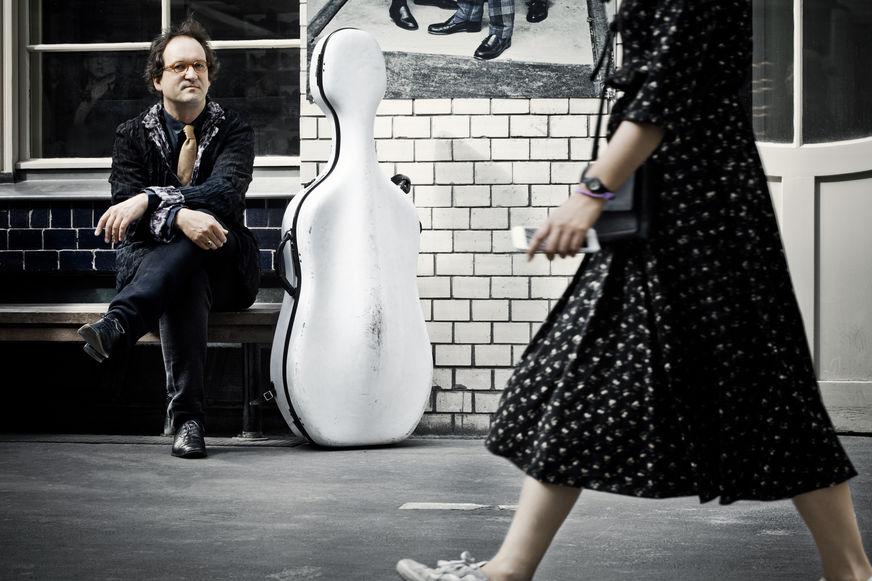 Lukas Dreyer in der Stadt auf einer Bank mit Cellokoffer