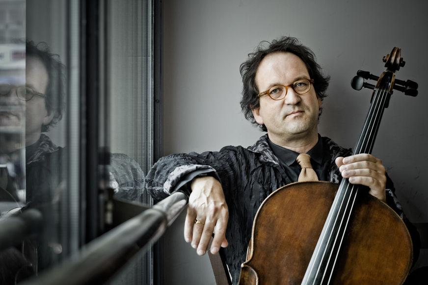 Lukas Dreyer mit seinem Cello spiegelt sich in der Scheibe