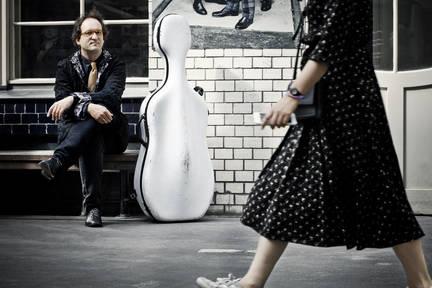 Ein Cellist sitzt auf einer Bank. Sein Cello steht neben ihm im weissen kasten. Er beobachtet in einem hof vvorübergehende Passanten. Hier eine Frau im Kleid im Anschnitt.
